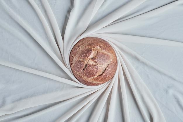 Bolo de pão redondo feito à mão no meio de um tabletloch.