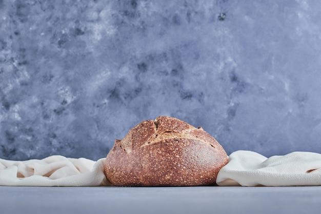 Bolo de pão redondo feito à mão sobre uma mesa azul.