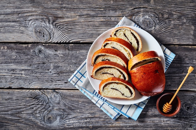 Bolo de papoula, makovnjaca, pão doce de massa doce com recheio de sementes de papoula, fatiado em um prato branco, cozinha croata, visão horizontal de cima, flatlay, close-up, espaço de cópia