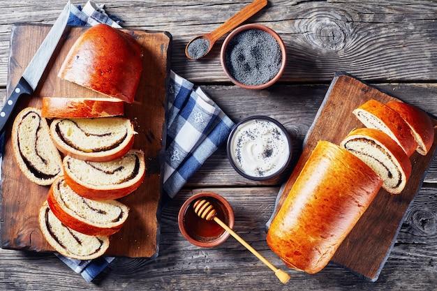 Bolo de papoula, makovnjaca, pão doce de massa doce com recheio de sementes de papoula, fatiado em uma placa de madeira, cozinha croata, ingredientes em uma mesa rústica, vista horizontal de cima, flatlay