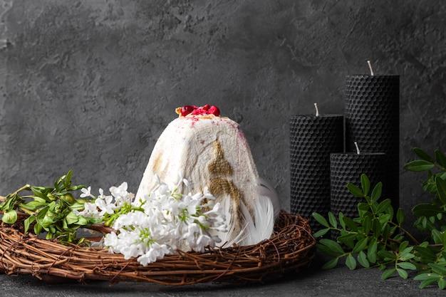 Bolo de páscoa branco kulich e velas rodeadas de folhas