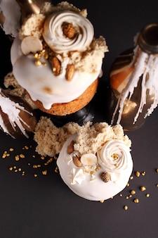 Bolo de páscoa com passas e frutas cristalizadas em esmalte branco é decorado com nozes, biscoito molecular e merengue