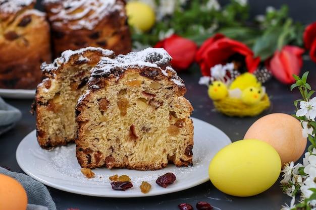 Bolo de páscoa cruffin e ovos coloridos em um fundo escuro, o conceito de feriado da igreja ortodoxa da primavera, orientação horizontal, closeup