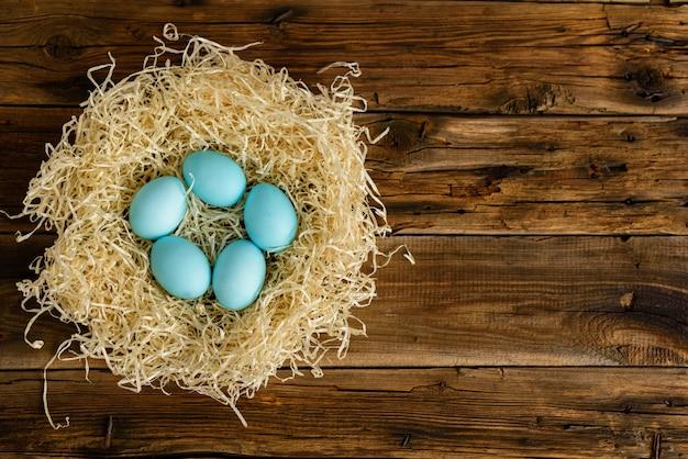 Bolo de páscoa e ovos coloridos em uma mesa de madeira.