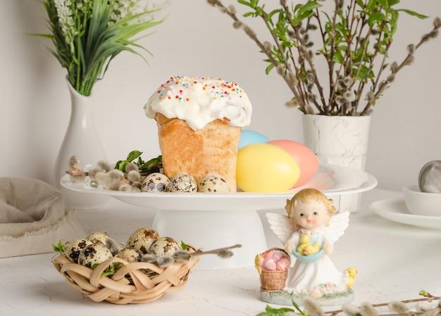 Bolo de páscoa e ovos coloridos em uma mesa de páscoa festiva com salgueiro e estatueta de anjo