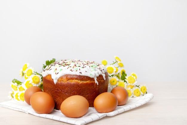 Bolo de páscoa e ovos coloridos flores amarelas de flores no fundo