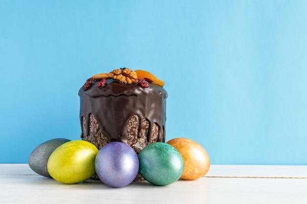 Bolo de páscoa e ovos coloridos sobre fundo azul. comida de férias e o conceito de páscoa.