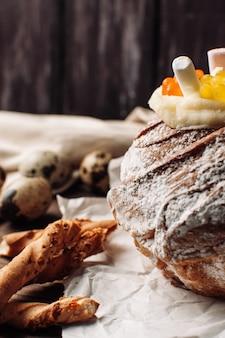 Bolo de páscoa elegante com marshmallows e ursinhos de geléia em papel pergaminho em um fundo de madeira rústico.