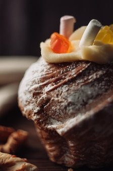 Bolo de páscoa elegante com marshmallows e ursinhos de geléia em um fundo escuro de madeira rústico.