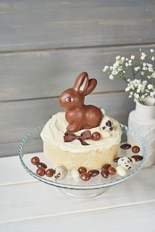 Bolo de páscoa rústico com coelhinhos de chocolate e ovos.