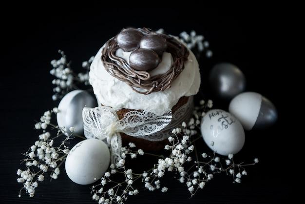 Bolo de páscoa tradicional com ovos pintados de prata, velas e salgueiro em uma mesa preta. foco seletivo