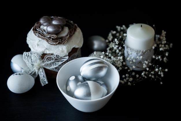 Bolo de páscoa tradicional com ovos pintados de prata, velas e salgueiro em uma superfície preta. foco seletivo