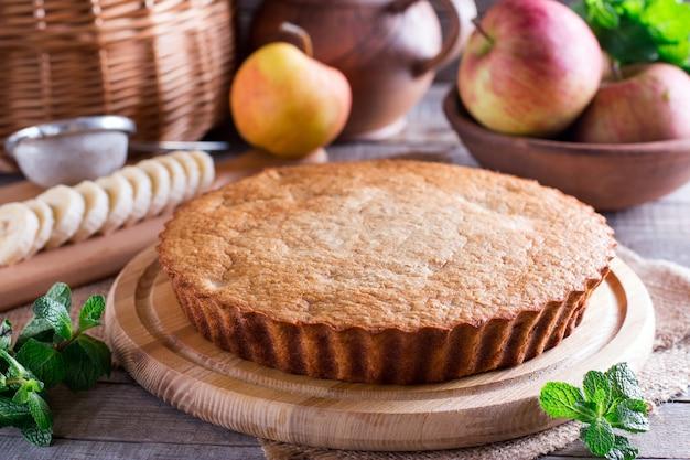 Bolo de pastelaria com maçã e banana em madeira