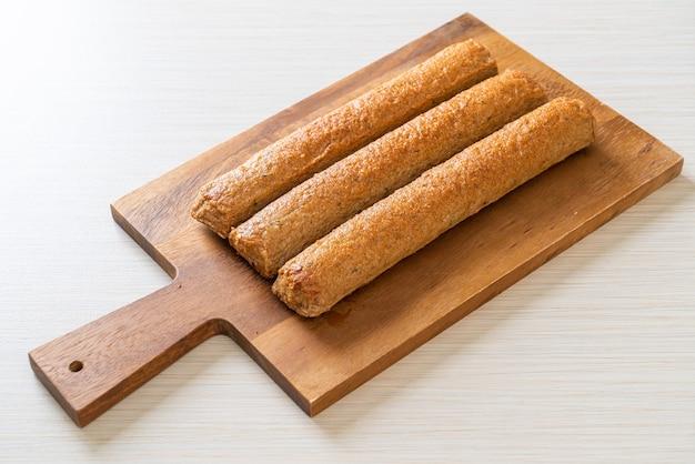 Bolo de peixe chinês frito ou linha de bola de peixe na placa de madeira