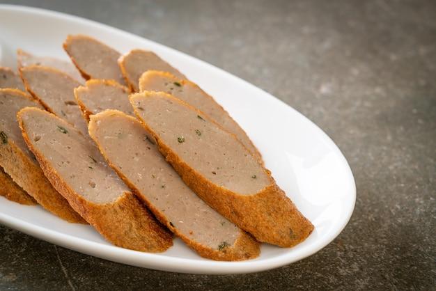 Bolo de peixe chinês frito ou linha de bolinho de peixe fatiado com molho picante de frutos do mar