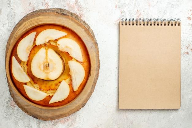 Bolo de pêra close-up, caderno, creme, bolo de pêra na tábua de madeira sobre a mesa branca