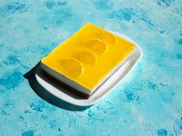 Bolo de queijo amarelo com laranjas em uma superfície azul brilhante