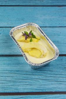 Bolo de queijo caseiro com cobertura de frutas durian, sobre um fundo azul de madeira