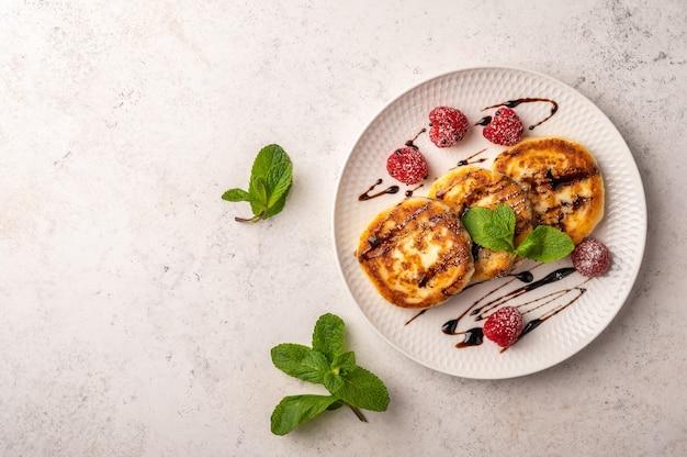 Bolo de queijo caseiro com framboesa, calda e hortelã em um prato de cerâmica sobre um fundo claro de madeira