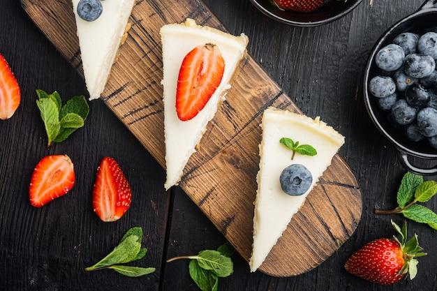 Bolo de queijo caseiro com frutas frescas, na mesa de madeira preta