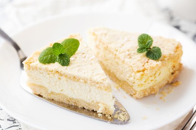 Bolo de queijo caseiro com queijo cottage em um prato branco decorado folhas de hortelã
