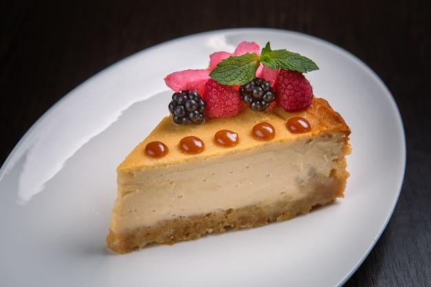 Bolo de queijo com bagas de amora, folha de hortelã em um prato branco