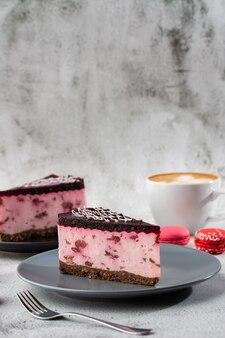 Bolo de queijo com cereja com café na mesa branca. closeup vista. saboroso café da manhã. pedaço de bolo na chapa preta, copo branco sobre fundo branco de mármore. foto vertical.