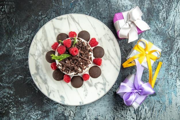Bolo de queijo com chocolate em prato oval e presentes de natal em superfície cinza