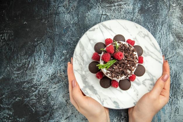 Bolo de queijo com chocolate em um prato oval em uma mulher com as mãos em um lugar livre de superfície cinza