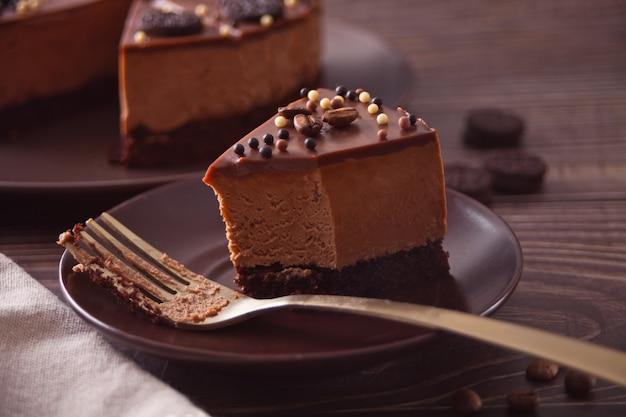 Bolo de queijo com chocolate na mesa de madeira com um garfo.