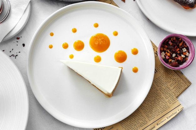 Bolo de queijo com creme de manga na mesa branca