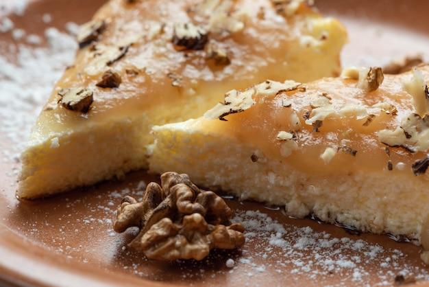 Bolo de queijo com creme e nozes desfiadas em um prato de terracota