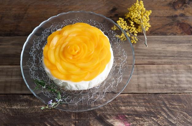 Bolo de queijo com decoração de pêssegos e flores amarelas em fundo de madeira. copie o espaço.