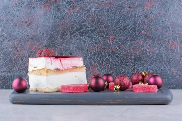 Bolo de queijo com doces e bolas de natal na chapa escura. foto de alta qualidade