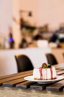 Bolo de queijo com frutas e hortelã na mesa de madeira no café