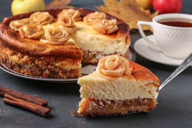 Bolo de queijo com maçãs decoradas com rosas de maçãs localizadas em uma superfície escura e xícara de chá, orientação horizontal