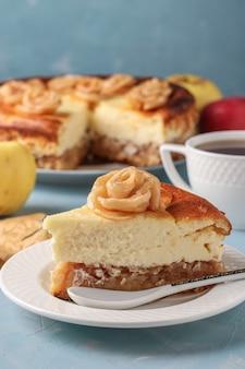 Bolo de queijo com maçãs, localizado em uma superfície azul claro, decorado com rosas de maçãs e xícara de chá, orientação vertical