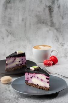 Bolo de queijo com mirtilo com xícara de café na mesa branca. closeup vista. saboroso café da manhã. pedaço de bolo na chapa preta, copo branco sobre fundo branco de mármore. foto vertical.
