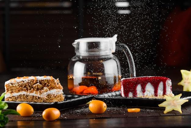 Bolo de queijo com molho de frutas vermelhas e bolo de cenoura com creme de leite e caramelo em pratos quadrados pretos sobre mesa de madeira escura