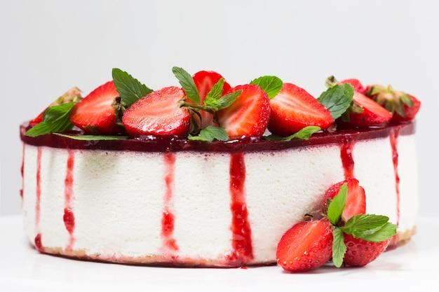Bolo de queijo com morangos em um prato branco, frutas frescas, folhas de hortelã