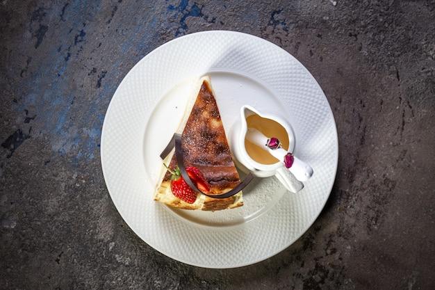 Bolo de queijo com recheio de queijo e morangos em um prato branco vista de cima