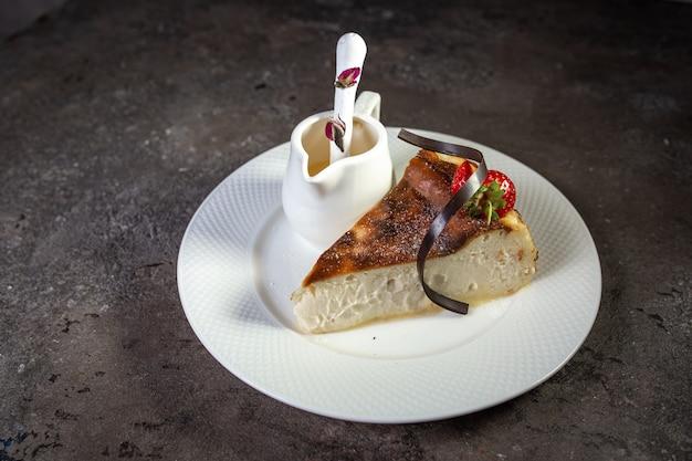 Bolo de queijo com recheio de queijo e morangos num prato branco