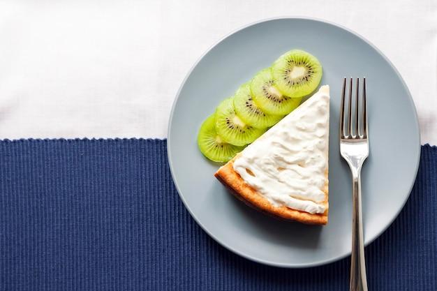 Bolo de queijo cottage caseiro com kiwis e creme em um prato. camada plana, vista superior, espaço de cópia