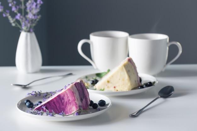 Bolo de queijo de frutas vermelhas e duas xícaras de chá na mesa branca na parede cinza de fundo