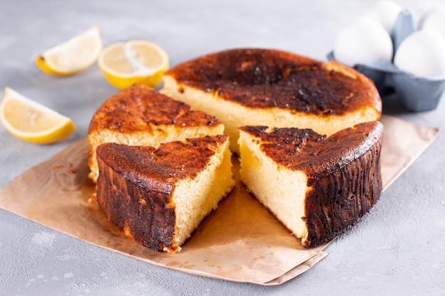 Bolo de queijo de san sebastian cortado e fatiado para servir em um fundo claro