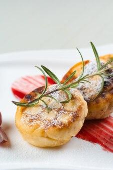 Bolo de queijo decorado com açúcar de confeiteiro, ramo de alecrim e uvas com geléia de baga em um prato branco. delicioso café da manhã com queijo cottage.