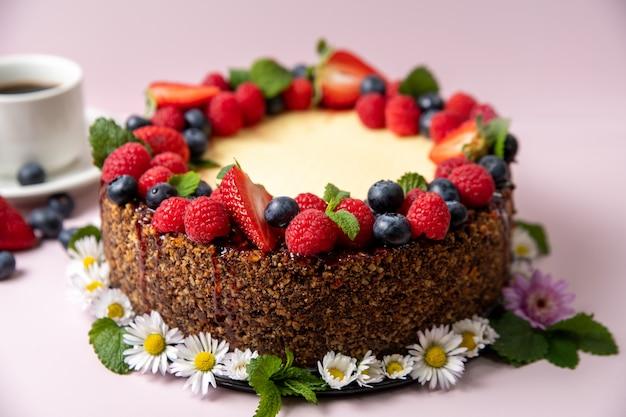 Bolo de queijo decorado com frutas e flores sobre um fundo rosa claro com uma xícara de café no lado esquerdo.