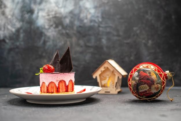 Bolo de queijo delicioso com morango e chocolate em prato oval vermelho natal árvore bola lanterna no escuro