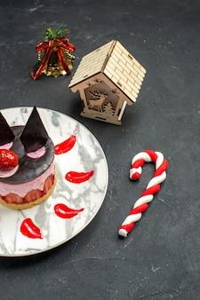 Bolo de queijo delicioso com morango e chocolate em uma placa oval de brinquedos de árvore de natal em fundo escuro vista frontal