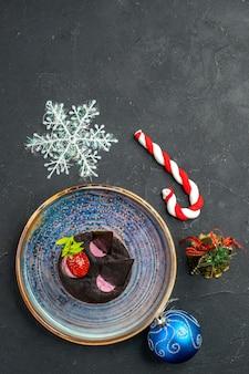 Bolo de queijo delicioso com morango e chocolate no prato brinquedos de natal no fundo escuro isolado.